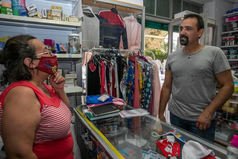 Juan Antonio Collantes, en la mercería de su barrio, con una de las vecinas fan de los textos de ánimo que publica