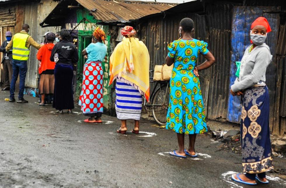 Several Mathare residents queue up to pick up food at neighborhood stores.