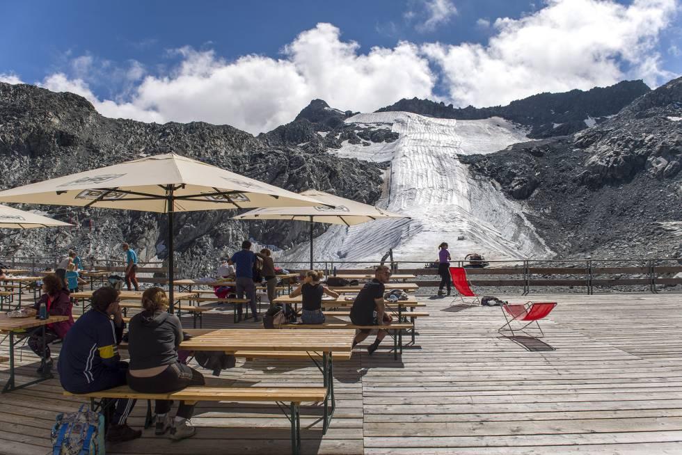 Turistas en el refugio Capanna Presena, frente a la pista de esquí cubierta.