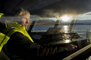 An operator drives the boat to the salmon-growing rings, located in the middle of the sea on the island of Skjervøya.