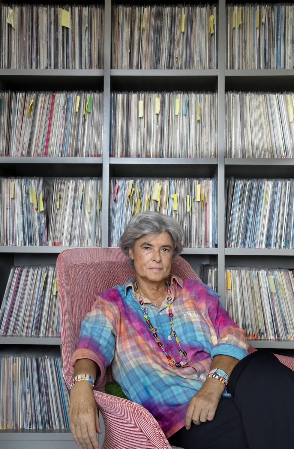 Gladys Palmera, with a shelf crammed with vinyl behind.