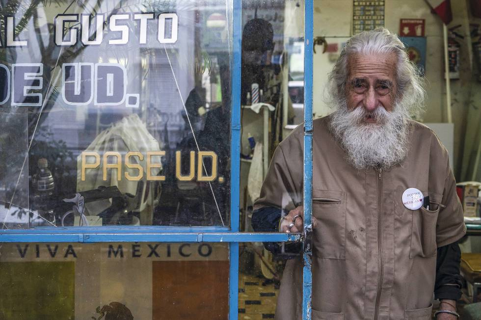 "Don Manuel at the door of the hairdresser.  The sign reads: ""Modern Cuts to Your Choice."""