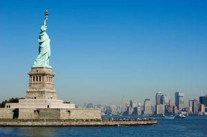 la estatua de la libertad y al fondo la isla de manhattan en