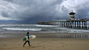 Una surfista junto al muelle de Huntington Beach, en California.