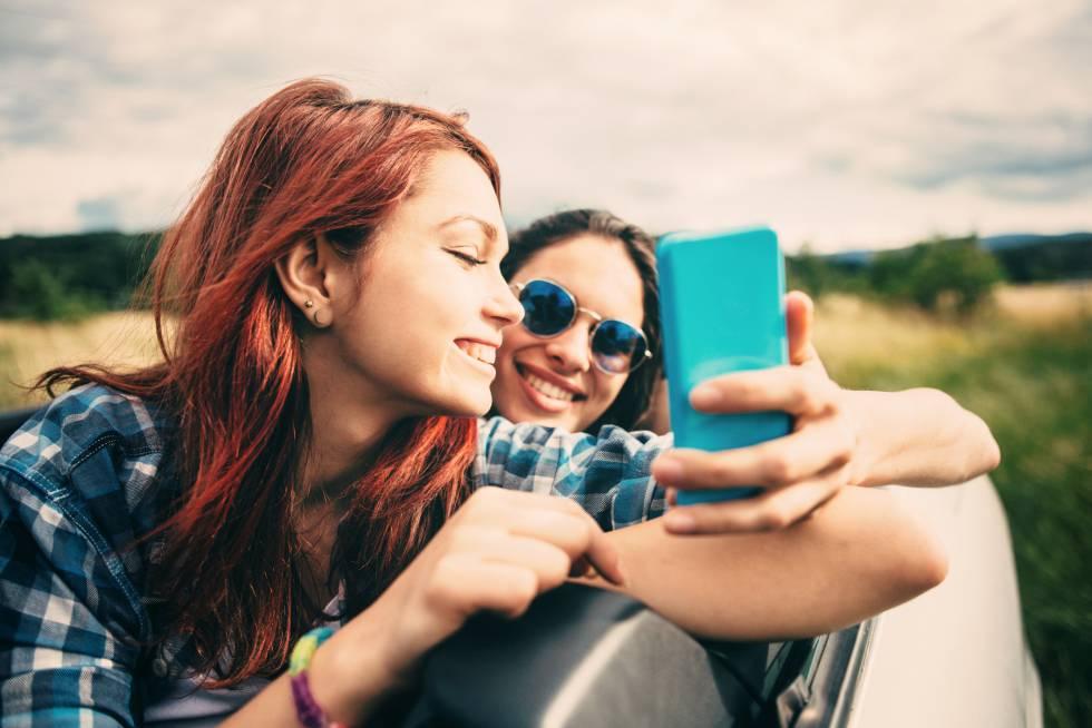 Dos jóvenes consultando un móvil.