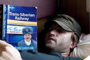 Un pasajero con una guía de viajes del Transiberiano.