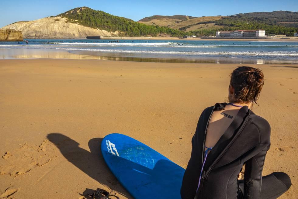 Una surfista descansa en la playa de Gorliz, en Bizkaia.