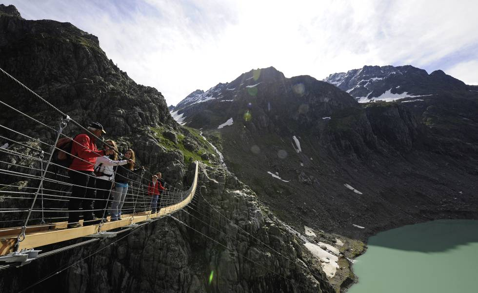 Turistas en el puente de Triftbrucke, en los Alpes suizos.