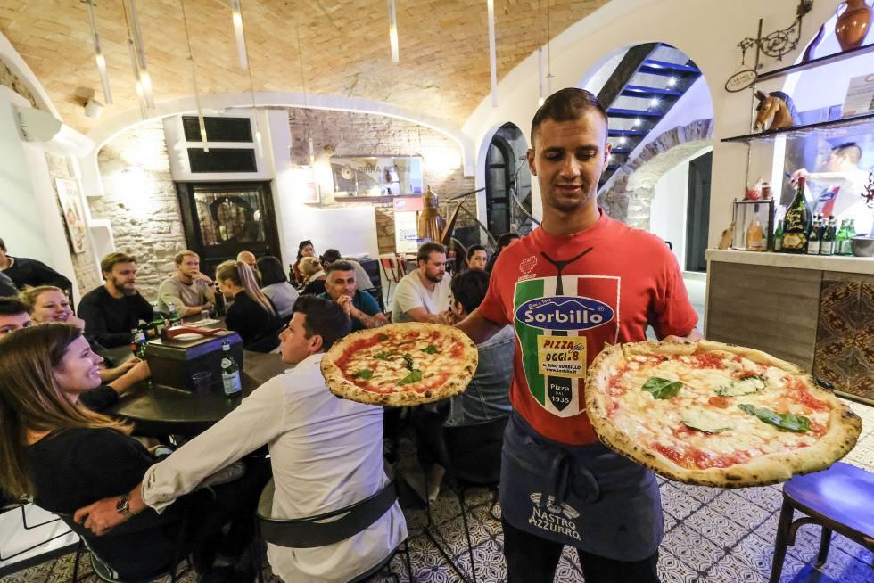 Un camarero sirve dos pizzas margarita en uno de los restaurantes Sorbillo en Nápoles.