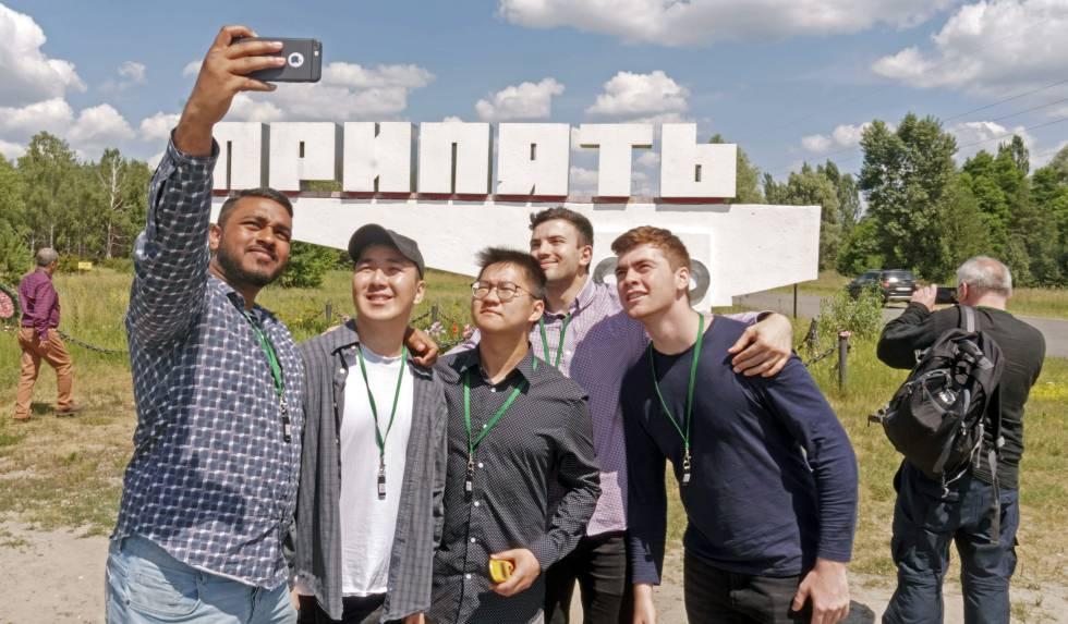 Turistas haciéndose un selfi con el cartel de la localidad ucrania al fondo.