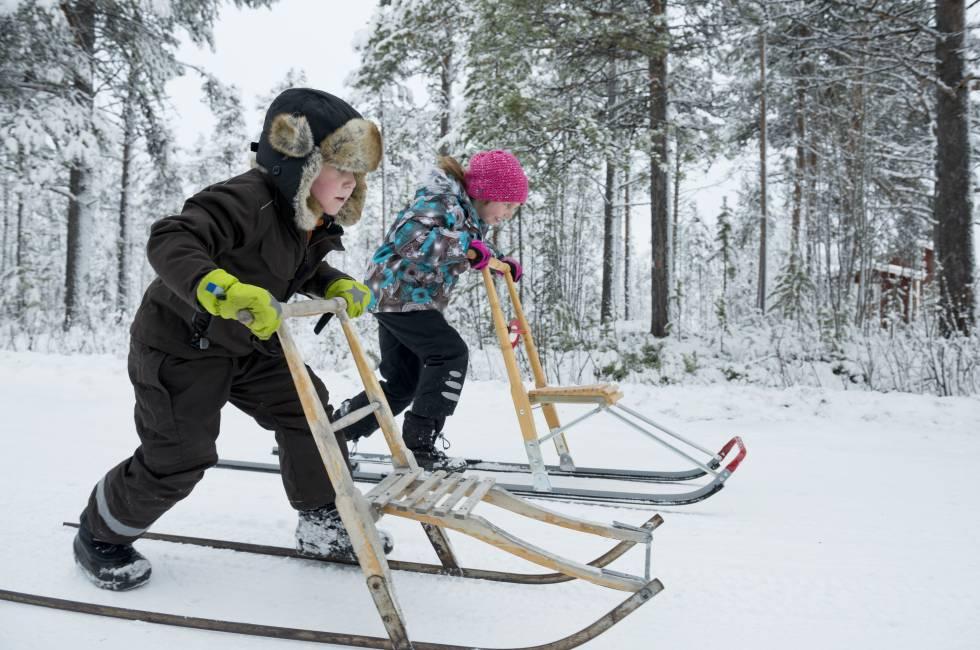 Dos niños con trineos de nieve en Laponia.