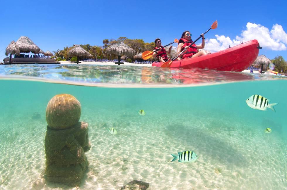 Una pareja en canoa y, bajo las aguas, unas ruinas mayas, en Roatán (Honduras).