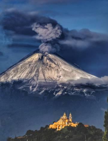 El santuario de Nuestra Señora de los Remedios y, al fondo, el volcán Popocatépetl (México), escenario de la novela Bajo el volcán.