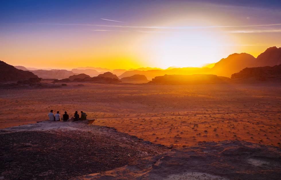Varias personas observan el amanecer en el desierto jordano de Wadi Rum.
