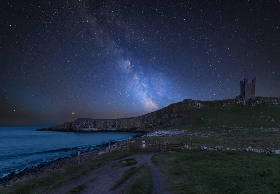 La Vía Láctea visible cerca del castillo de Dunstanburgh, en la costa de Northumberland (Inglaterra).