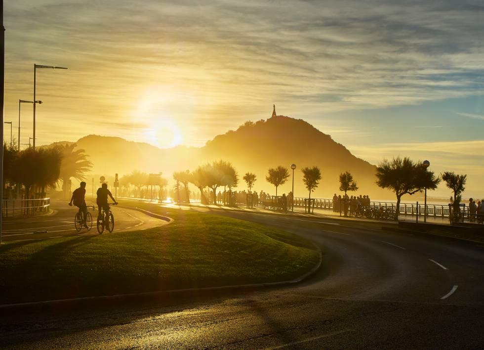 Dos ciclistas pedalean en San Sebastián mientras el sol se pone detrás del Monte Urgull.