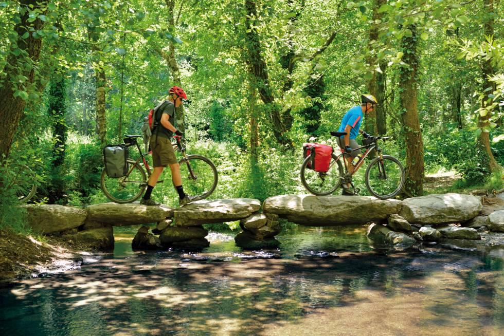 Unos ciclistas sortean un río en Galicia durante su peregrinaje por el Camino de Santiago.