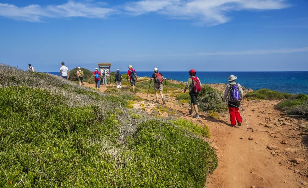 Senderistas en el Camí de Cavalls, cerca de cala Pilar, en la costa norte de Menorca.