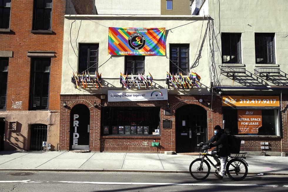 Un hombre con mascarilla y bicicleta pasa junto a la entrada de The Stonewall Inn (Nueva York), el bar que dio origen a las marchas del Orgullo.