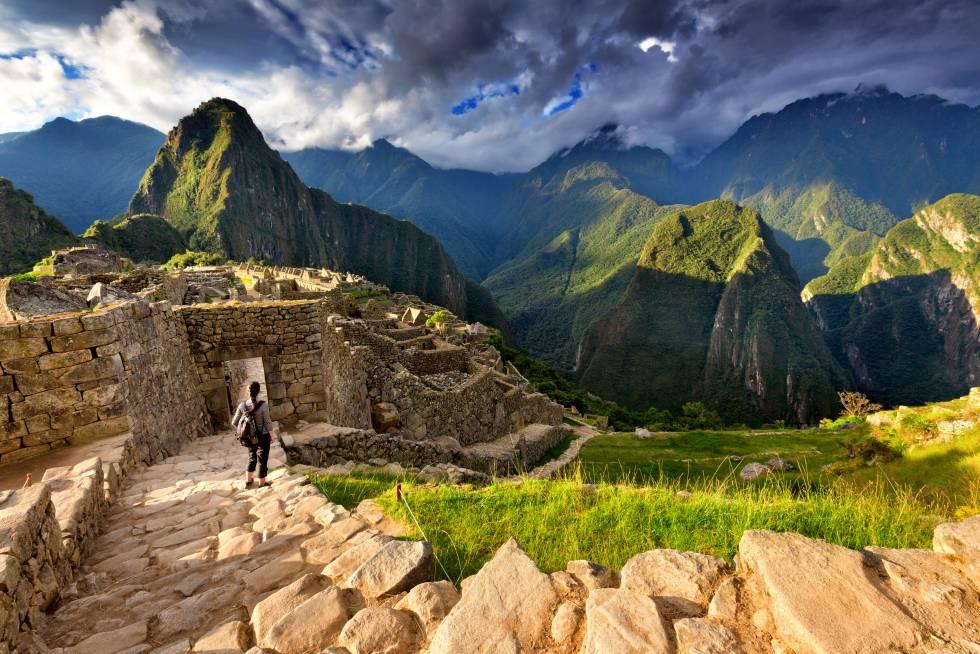 Una turista desciende unas escalinatas de piedra en la ciudadela de Machu Picchu.