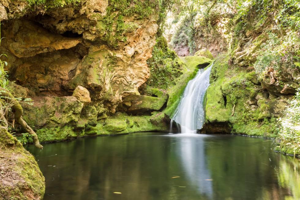 Una cascada cae sobre una piscina natural en los Baños de Popea, en Córdoba.