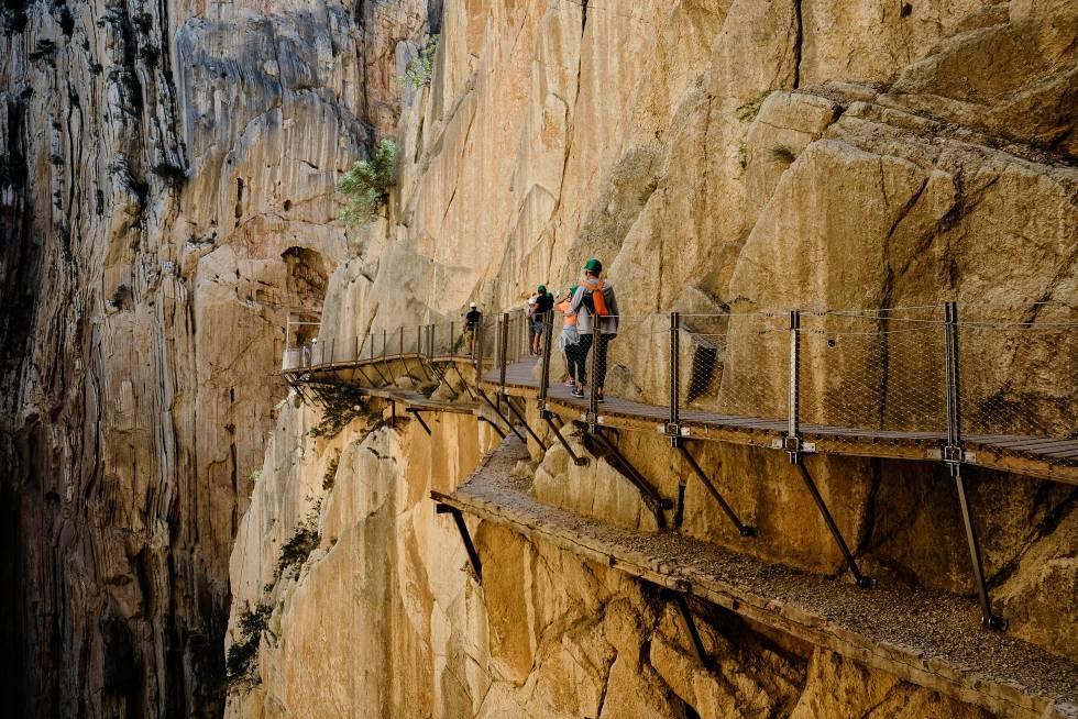 Un grupo atraviesa el desfiladero de El Chorro, en el Caminito del Rey (Málaga).