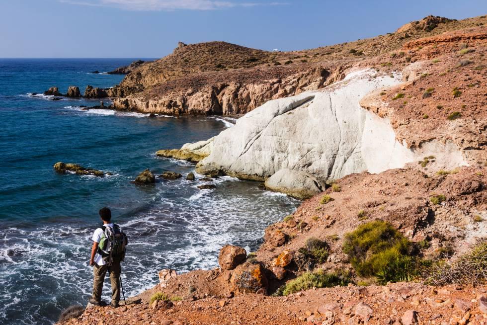 Un senderista se asoma a una de las calas del parque natural de Cabo de Gata-Níjar, en Almería.