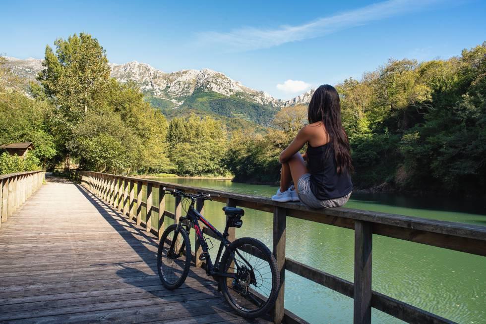 Una ciclista hace un alto en la Senda del Oso, en el puente que atraviesa el embalse de Valdemurio, en Asturias.