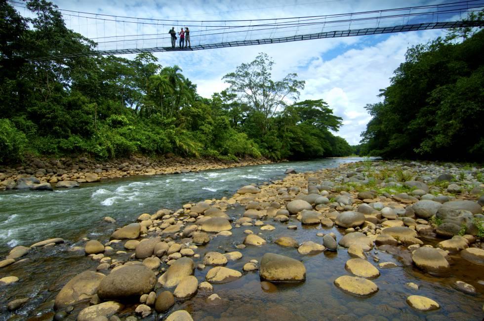 Turistas disfrutan de las vistas desde un puente colgante sobre e río Sarapiquí, en la reserva biológica de Tirimbina, al norte de Costa Rica.