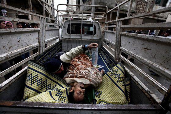 Un herido es trasladado en Homs con precaución para evitar a los francotiradores.