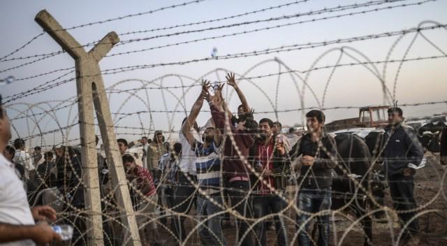 Curdos sírios em Suruc, no lado sírio da fronteira, em 21 de setembro. / Foto: AFP   Vídeo: ATLAS