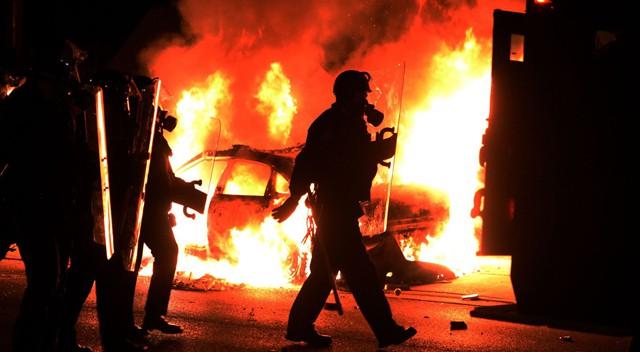 Policiais caminham entre carros queimados após decisão.