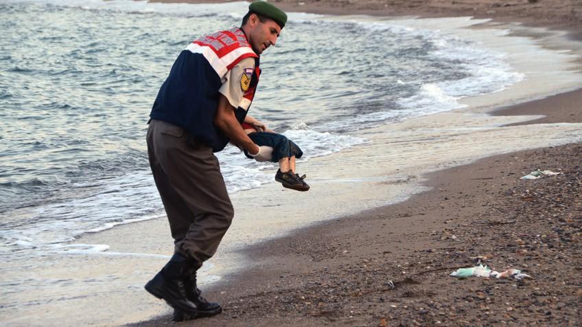Um policial recolhe o cadaver de uma criança em uma praia de Turquia.