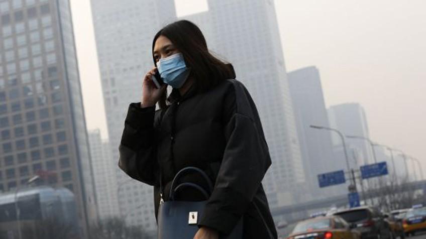 Mulher caminha por Pequim, nesta segunda-feira.