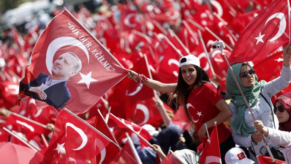 Dois jovens agitam bandeiras da Turquia e com a efígie de Erdogan