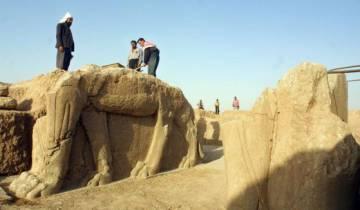 Trabajadores limpian una estatua en un yacimiento arqueológico en Nimrud.