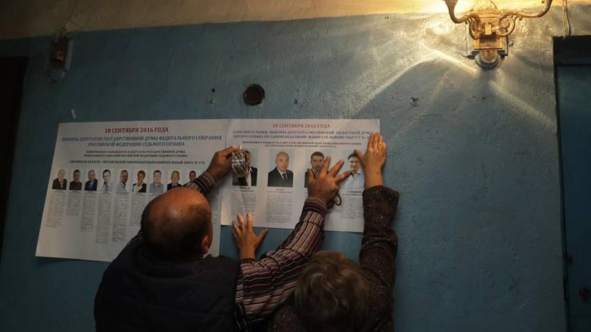 Funcionários de um colégio colocam panfletos eleitorais em Gusino, no oeste da Rússia.