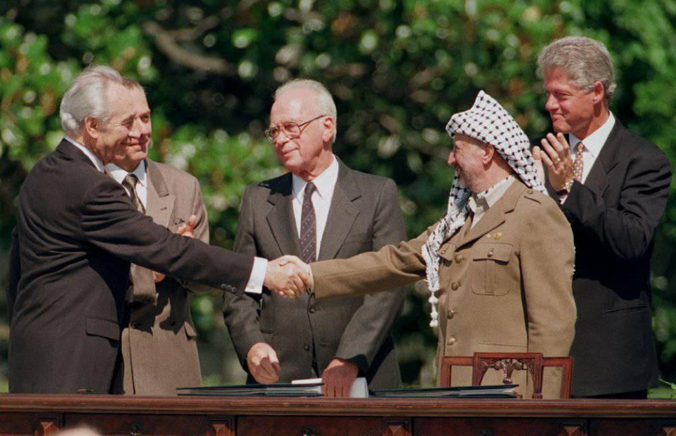 El ministro de Exteriores de Israel Simon Peres (i) saluda al presidente de la Organización para la Liberación de Palestina, Yasir Arafat (d), durante la firma del acuerdo de paz para Oriente Medio de Washington, en 1993.
