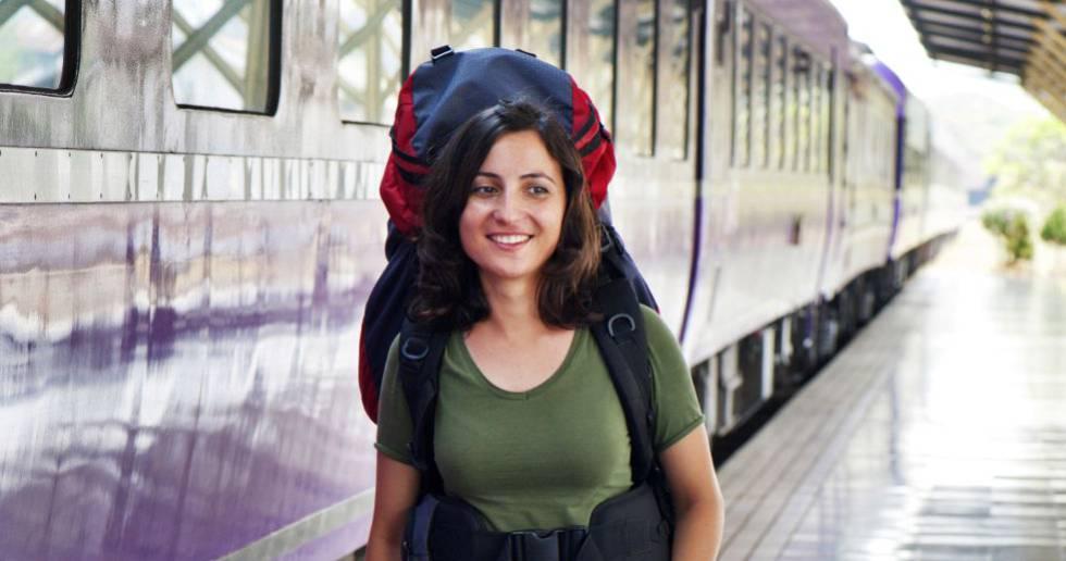Una joven mochilera camina en una estación de tren.