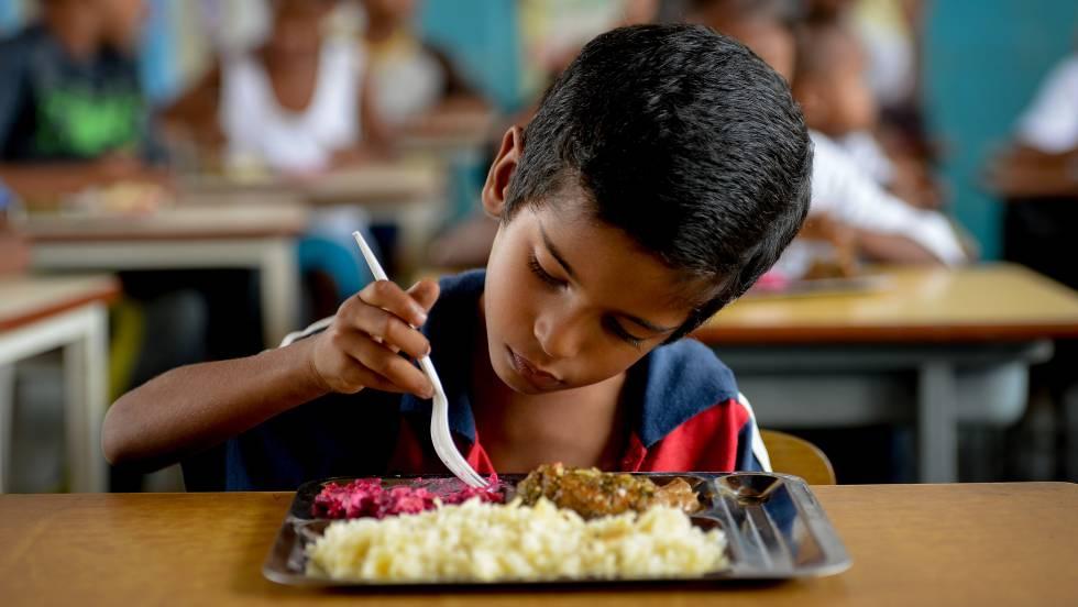 Um menino almoça num refeitório escolar de Higuerote, em agosto.