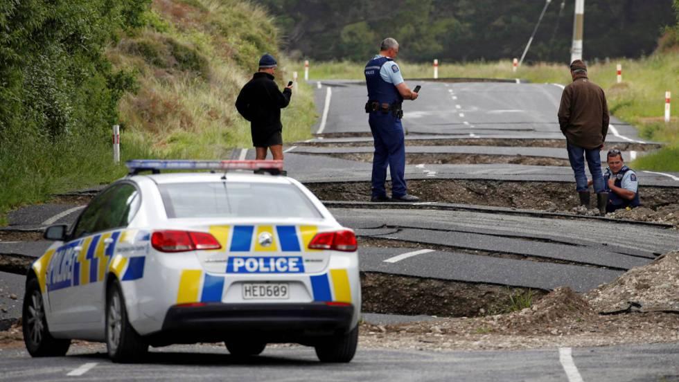 A policial avalia os danos do seísmo em uma estrada de Blenheim, na ilha sul de Nova Zelândia.