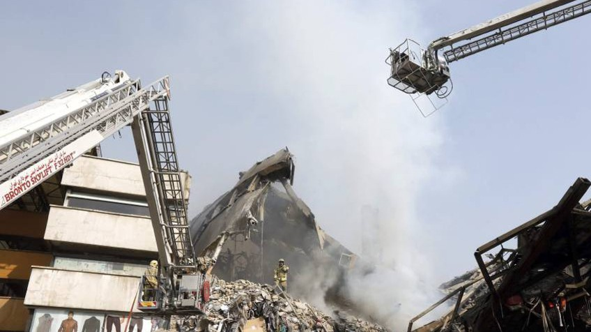 Membros dos serviços de resgate iranianos buscam possíveis vítimas entre os escombros do edifício Plasco.