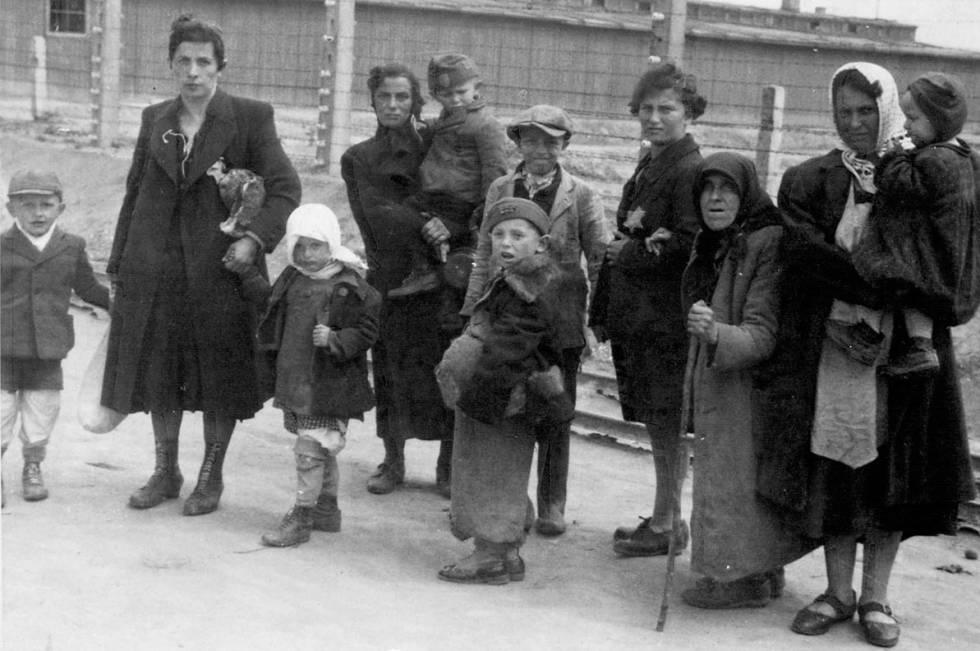 Mulheres judias com seus filhos caminham para as câmaras de gás.