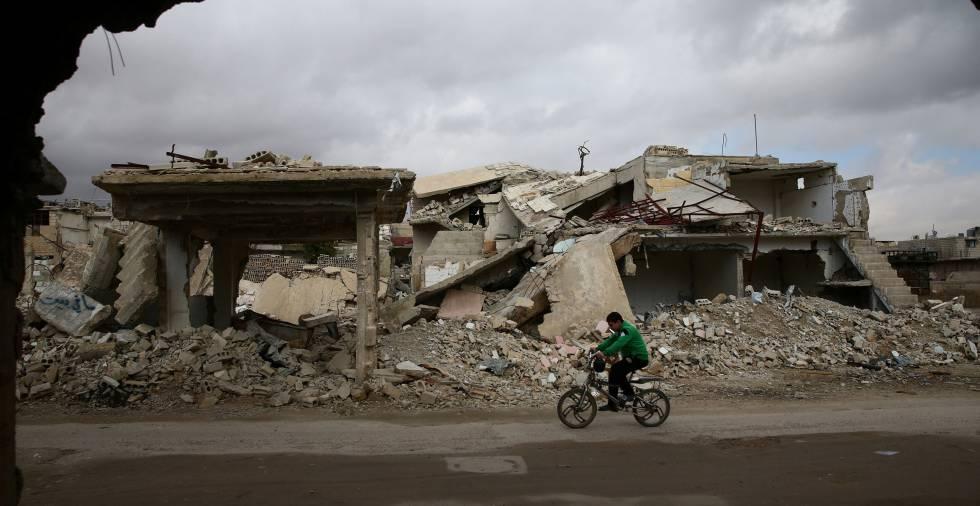 Un niño recorre en bicicleta las ruinas de la ciudad de Douma en Siria.