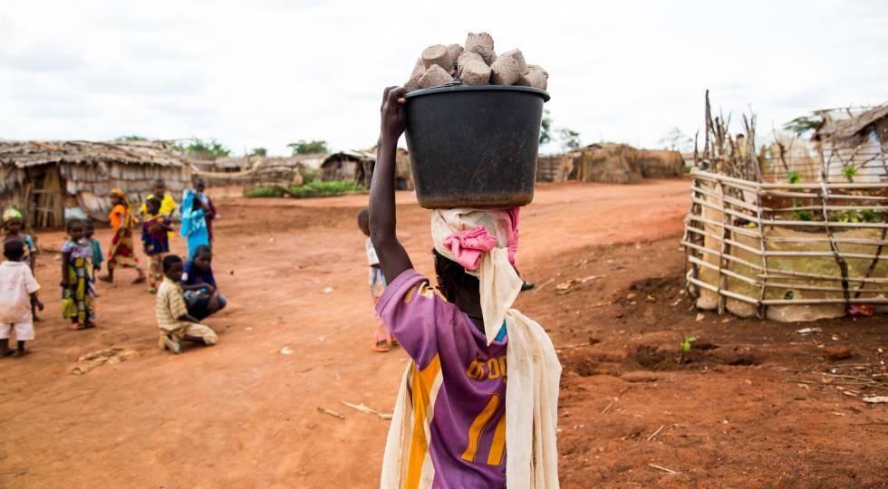 Una joven carga un cubo con pastillas de combustible en el campo de refugiados de Mbilé (Camerún).