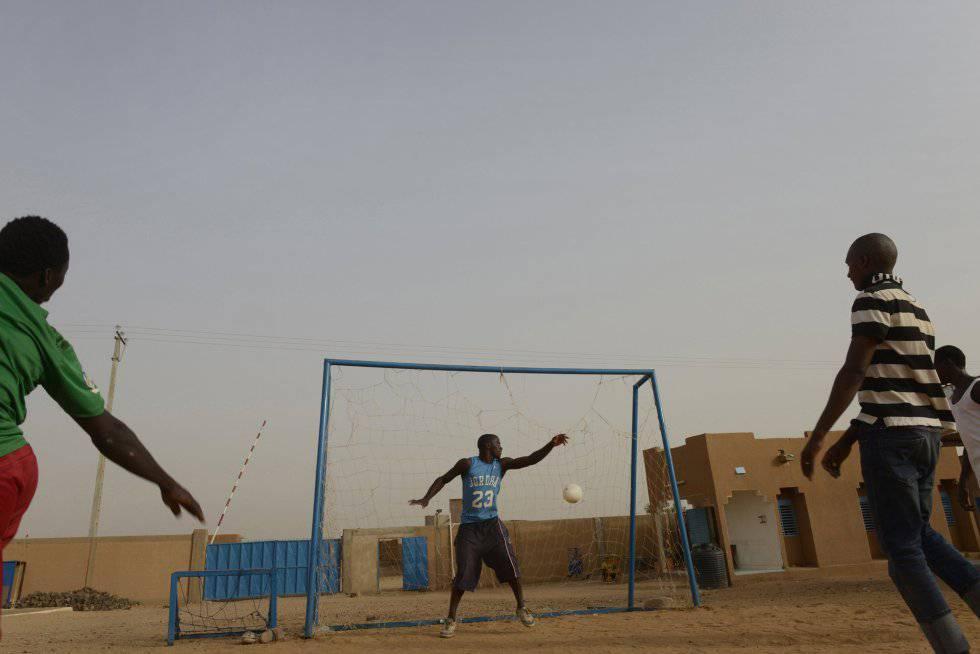 Migrantes jogam futebol no pátio central de um centro de acolhida da OIM.