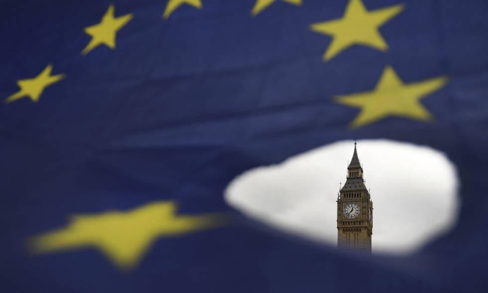 El Big Ben asoma por un roto en una bandera de la Unión Europea en Londres.