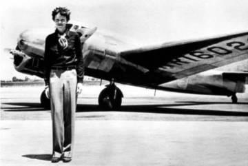 Amelia Earhart junto al bimotor con el que se estrelló.