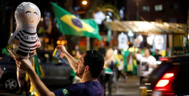 Homem sustenta o 'Pixuleco', um balão do ex-presidente Lula vestido como um réu, em um protesto.