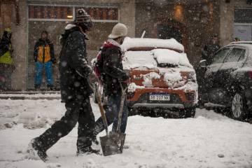 La nieve obliga a algunos barilochenses a llevar la pala al trabajo.
